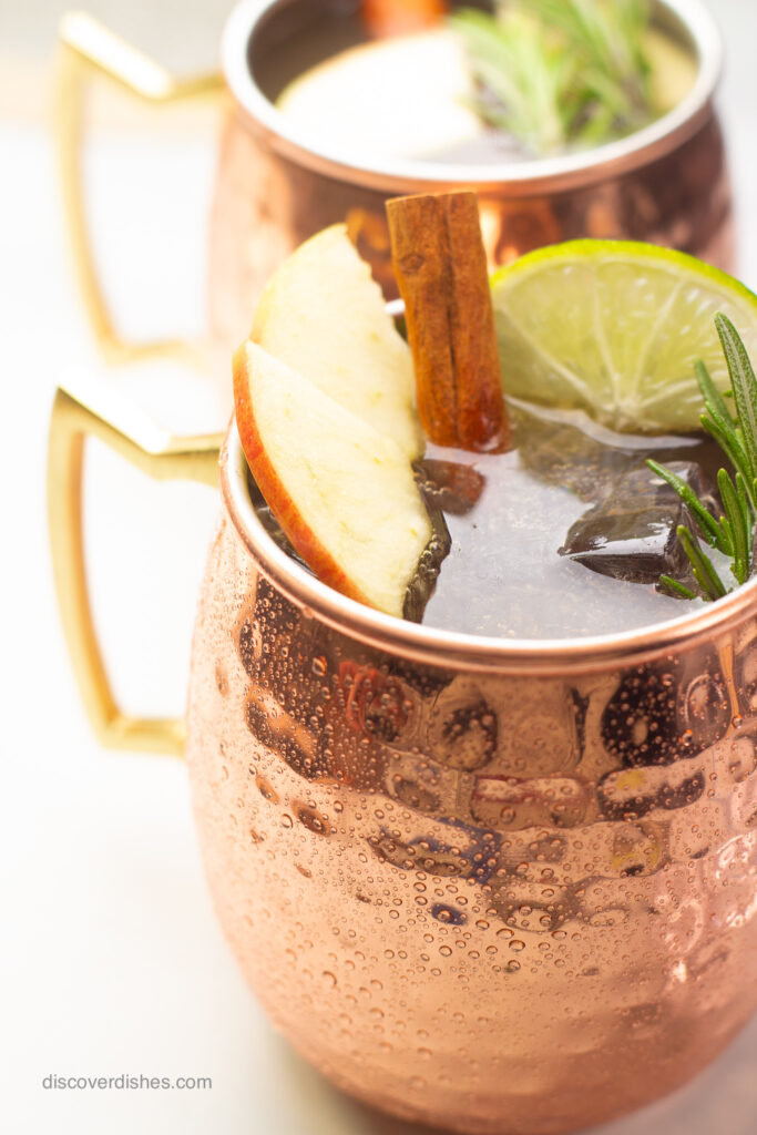 An apple cider moscow mule garnished with apples, limes, cinnamon sticks, and rosemary.