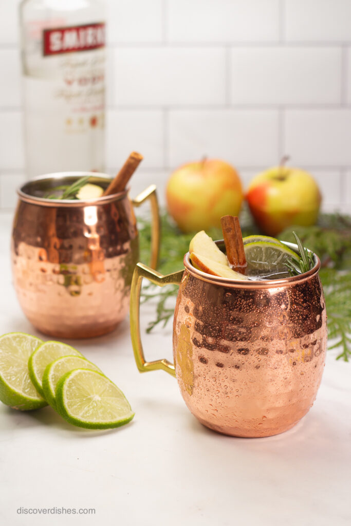Two copper mugs filled with moscow mules and garnished with cinnamon sticks.
